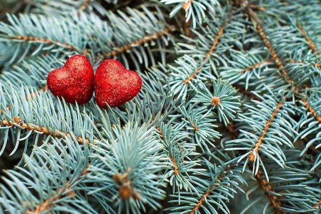 Fond de branches de noël avec deux coeurs rouges brillants sur eux. copier l'espace