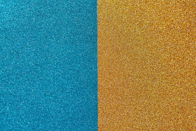 Fond brillant lumineux et festif, composé de deux moitiés, bleu et or. horizontal.