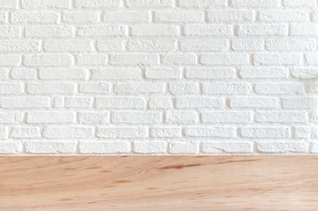 Fond de brique blanche sur une surface en bois. pour le placement des pièces à présenter