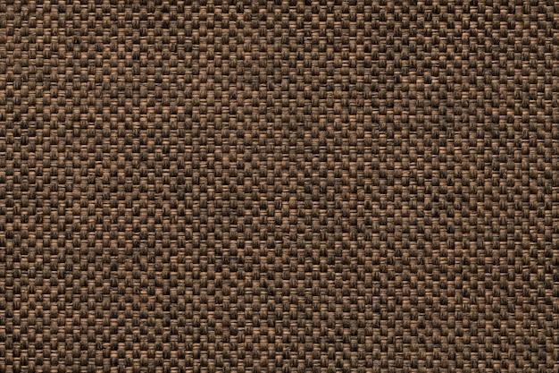 Fond brun foncé de tissu d'ensachage tissé dense, gros plan. structure de la macro textile.