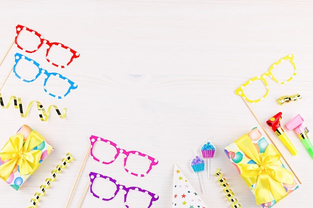 Fond avec des cadeaux emballés, confettis, chapeaux de fête, décorations, espace copie
