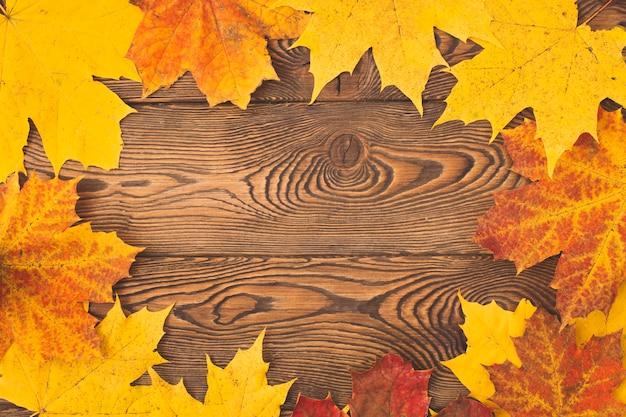 Fond de cadre d'érable couleur automne feuilles sur une table en bois