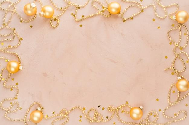 Fond de cadre de noël doré. perles avec des boules décoratives et des étoiles.