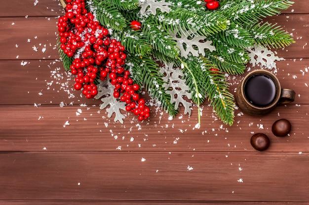 Fond de café chaud de noël. sapin du nouvel an, rose des chiens, feuilles fraîches, bonbons au chocolat et neige artificielle.