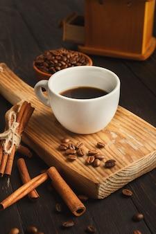 Fond de café du matin. tasse d'americano amer, haricots et épices sur planche de bois rustique, espace pour copie