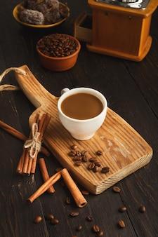 Fond de café du matin. tasse de cappuccino laiteux, haricots et épices sur planche de bois rustique, espace pour copie