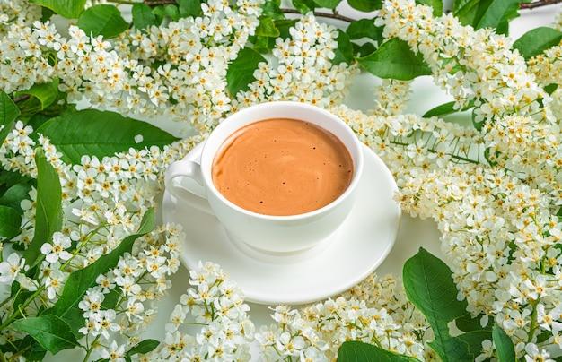 Fond de café avec des fleurs, vue latérale, horizontale. une tasse à cappuccino blanche parmi des fleurs blanches.