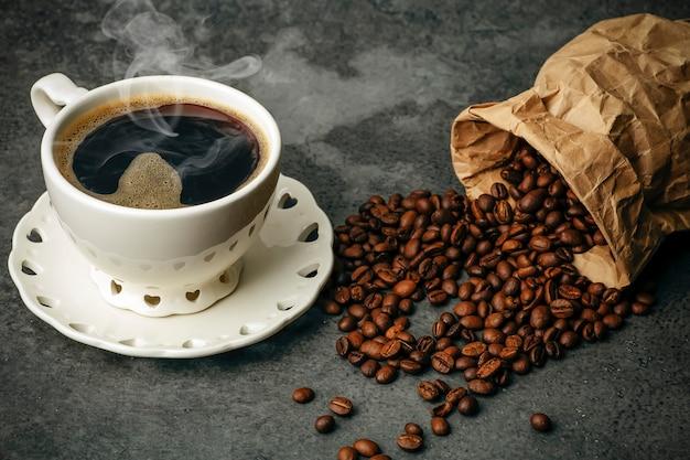 Fond de café. grains de café et tasse sur fond sombre. bannière de café pour le menu, la conception et la décoration