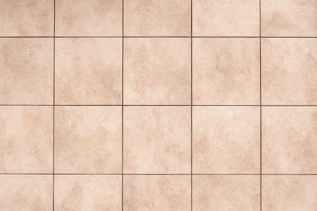 Fond de carreaux de céramique beige sur le sol