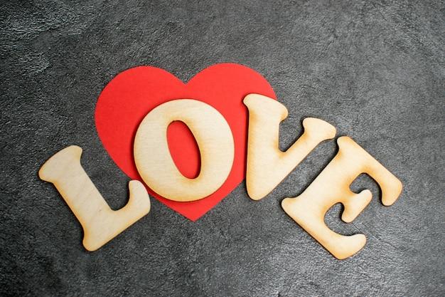 Fond de carte de saint valentin, coeur mignon rouge en papier avec mot en bois décoratif sur fond sombre. saint valentin romantique. l'amour