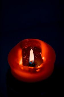Fond de carte de voeux de joyeuses fêtes et concept de saison d'hiver bougie de vacances rouge sur fond sombre...