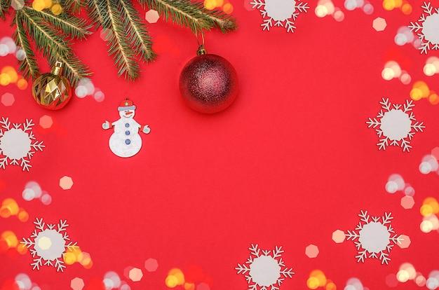 Fond de carte de voeux joyeux noël avec un bonhomme de neige, des branches d'arbres de noël et des boules avec un cadre bokeh.