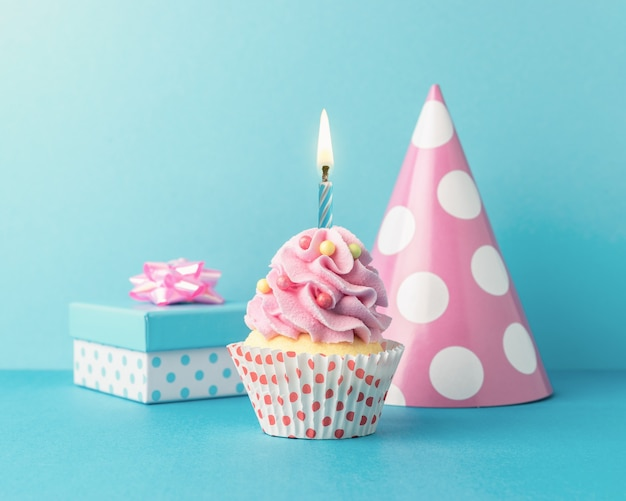 Fond de célébration colorée avec diverses décorations de fête et cupcake.