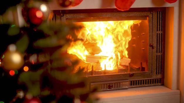 Fond de célébrations d'hiver avec cheminée en feu et arbre de noël décoré dans le salon