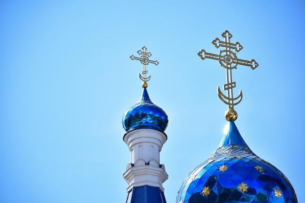 Sur fond de ciel bleu clair, deux dômes d'une église chrétienne ou d'un monastère de différentes tailles, avec des croix en haut