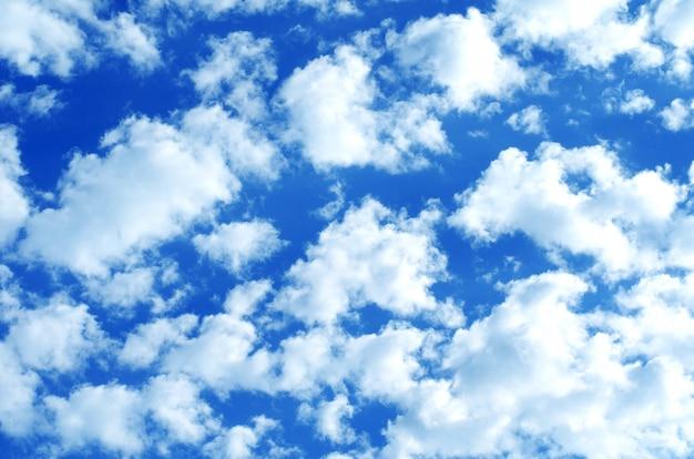 Fond de ciel bleu avec des nuages blancs et gris.