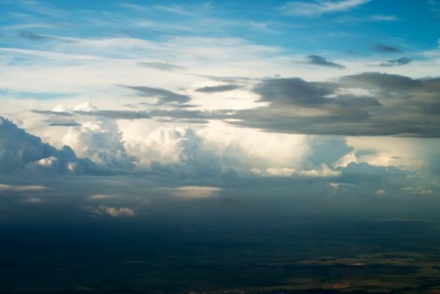 Fond de ciel bleu avec des nuages blancs. nuages gonflés à l'horizon. vue depuis le hublot de l'avion. atmosphère de la terre bleu ciel jour, fond bleu foncé transparent