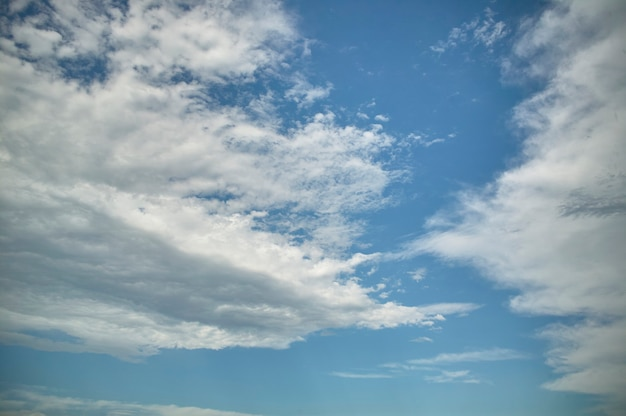 Fond avec ciel bleu en pleine journée avec quelques nuages blancs.