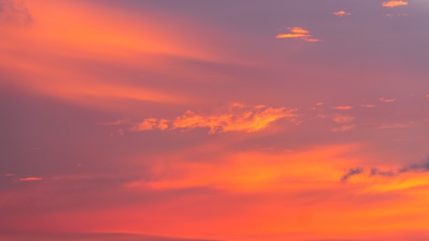 Fond de ciel coucher de soleil coloré avec des nuages de lumière du soleil orange dans le ciel au crépuscule du soir