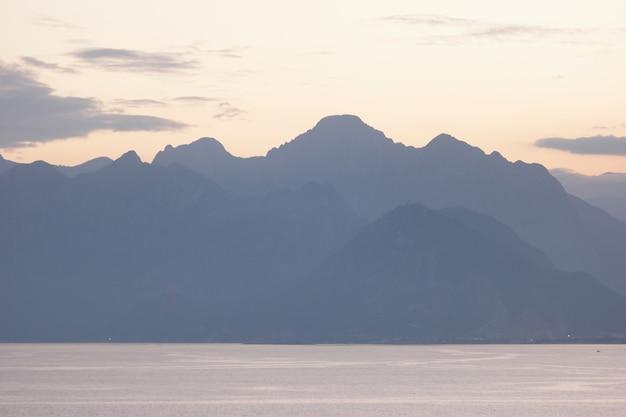Fond de ciel coucher de soleil avec la silhouette de la chaîne de montagnes.