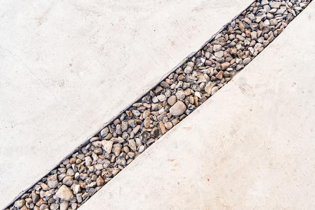 Fond de ciment traversé par une ligne diagonale de galets