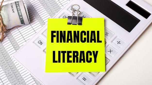 Sur un fond clair - de l'argent, une calculatrice blanche et un autocollant jaune sous un trombone noir avec le texte littératie financière. concept d'entreprise
