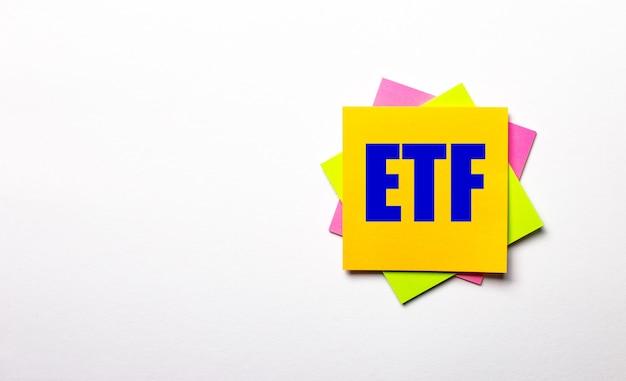 Sur un fond clair - autocollants multicolores lumineux avec le texte etf exchange traded funds. copier l'espace