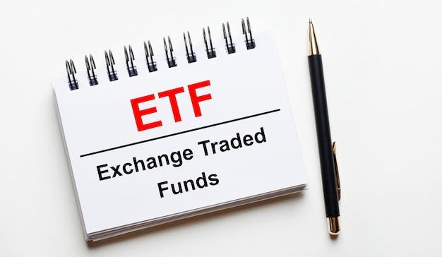Sur un fond clair, un cahier blanc avec des mots etf exchange traded funds et un stylo