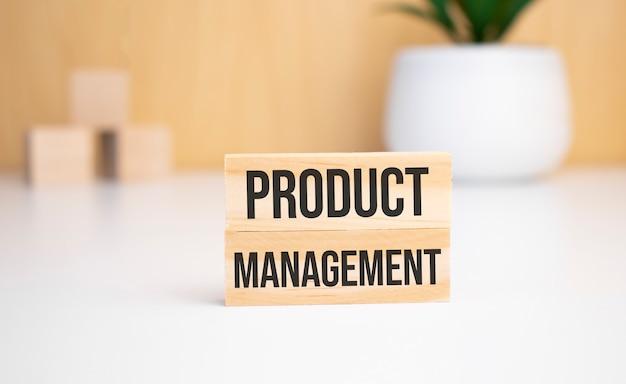 Sur un fond clair, des cubes en bois et un bloc de bois avec le texte gestion des produits, vue d'en haut