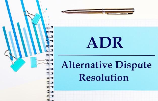 Sur un fond clair - des diagrammes bleu clair, des trombones et une feuille de papier avec le texte adr alternative dispute resolution. vue d'en-haut. concept d'entreprise