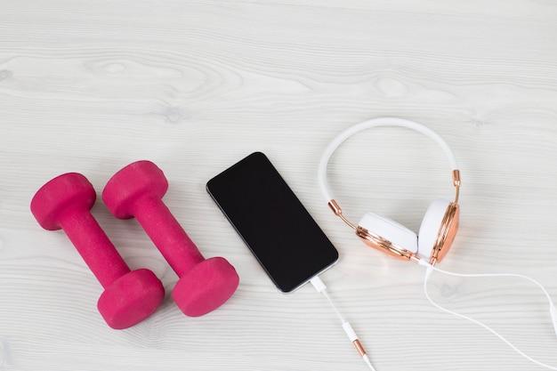 Sur un fond clair des écouteurs, un téléphone portable et des haltères