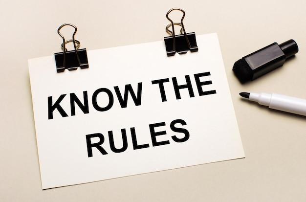 Sur fond clair, un feutre noir ouvert et sur des clips noirs une feuille blanche avec le texte connaître les règles