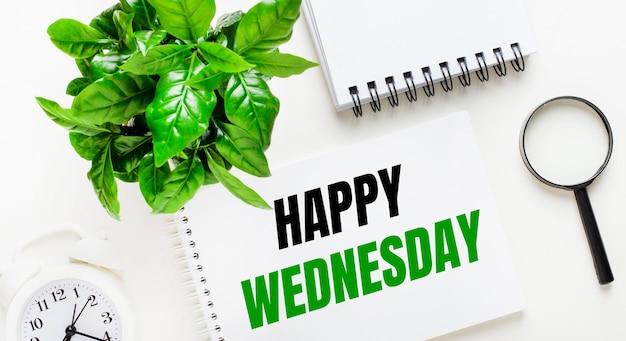 Sur un fond clair, il y a un réveil blanc, une loupe, une plante verte et un cahier avec les mots happy wednesday.
