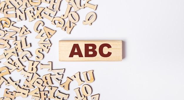 Sur un fond clair, des lettres en bois et un bloc en bois avec le texte abc. mise à plat