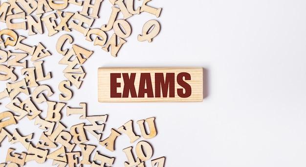 Sur un fond clair, des lettres en bois et un bloc en bois avec le texte exams. mise à plat