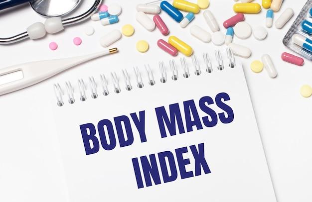 Sur un fond clair, des pilules multicolores, un stéthoscope, un thermomètre électronique et un cahier avec le texte body mass index. notion médicale.