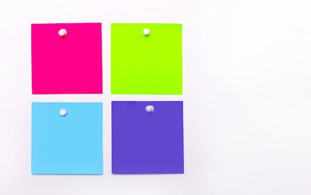 Sur fond clair, quatre stickers multicolores lumineux pour les notes. copier l'espace