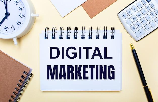 Sur fond clair, un réveil blanc, une calculatrice, un stylo et un cahier avec le texte digital marketing. mise à plat