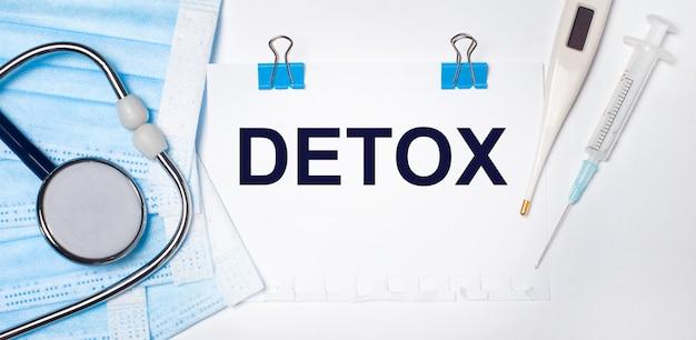 Sur un fond clair se trouvent un stéthoscope, un thermomètre électronique, une seringue, un masque facial et une feuille de papier avec le texte detox. notion médicale