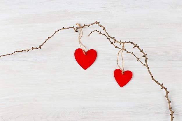 Sur un fond clair, une vieille branche et deux coeurs en bois rouge