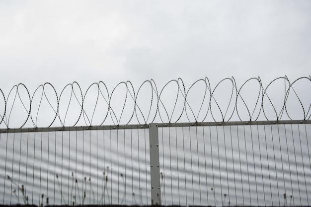 Fond d'une clôture avec des barbelés sous un ciel sombre