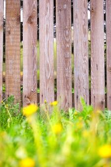 Fond de clôture en bois avec bordure d'herbe