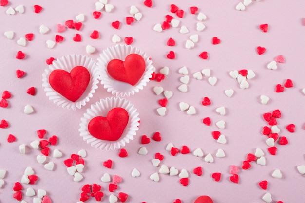 Fond de coeur de bonbons de saint valentin de paillettes rouges, blanches et roses