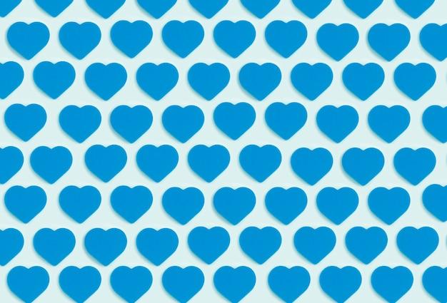 Fond de coeurs. motif d'ornement coloré à partir de coeurs bleus découpés sur fond bleu. amour, romance, papier peint, concept minimal de carte postale