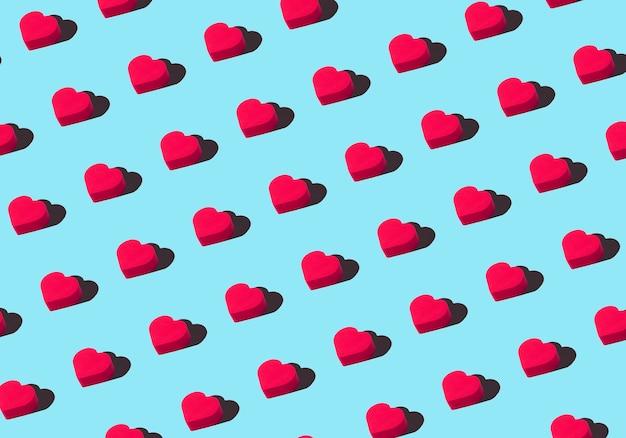 Fond de coeurs. motif d'ornement coloré à partir de coeurs rouges découpés sur fond bleu. amour, romance, papier peint, concept minimal de carte postale