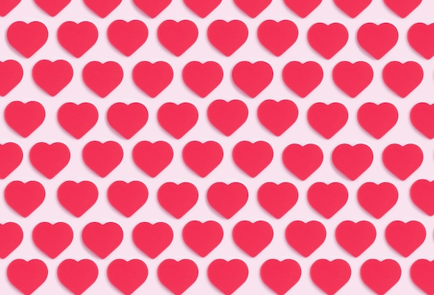 Fond de coeurs. motif d'ornement coloré à partir de coeurs rouges découpés sur fond rose. amour, romance, papier peint, concept minimal de carte postale