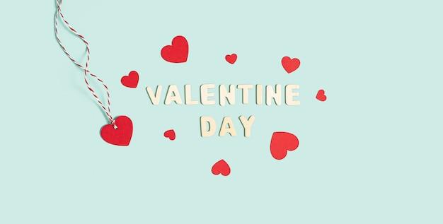 Fond avec des coeurs rouges et blancs avec texte de la saint-valentin sur fond bleu pastel