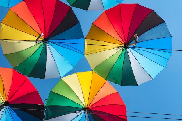 Fond coloré de beaux parapluies contre le ciel bleu