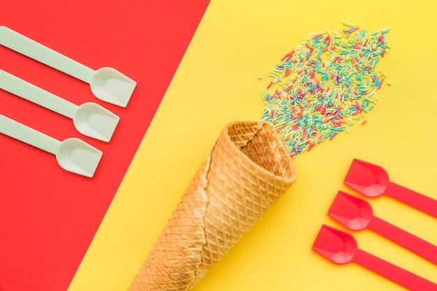Fond coloré avec des cuillères et du cône de glace