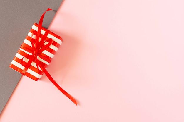 Fond coloré lumineux festif, cadeau avec ruban et arc sur papiers colorés